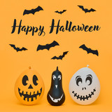 Cute Halloween pumpkins with funny smiling faces and paper bats flying over orange background. Halloween concept. - 226055788