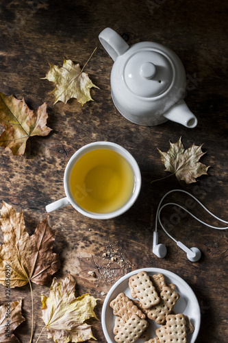Leinwandbild Motiv Cozy autumn still life on a wooden background - green tea, whole grain biscuits, headphones, dry maple leaves. Top view, flat lay