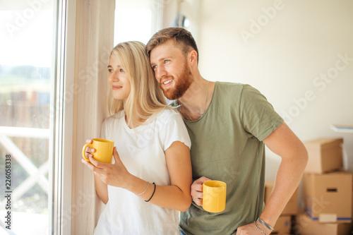 Leinwandbild Motiv man and woman drinking tea near window. Bought new house or apartment, start new life