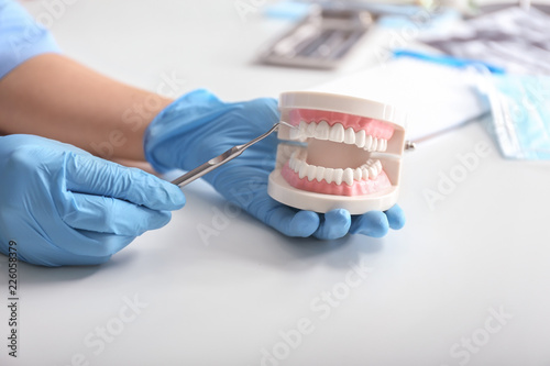 Leinwanddruck Bild Dentist with artificial jaw and dental tool at light table
