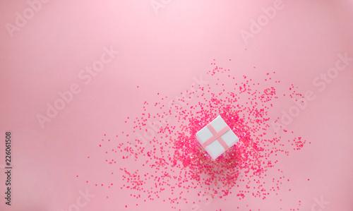 Białe pudełko z różowym brokatem na różowym tle