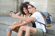 young couple taking selfie while sitting