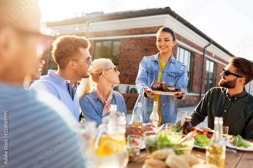 leisure and people concept - happy party host offering meat to his friends at barbecue party on rooftop in summer - 226069990