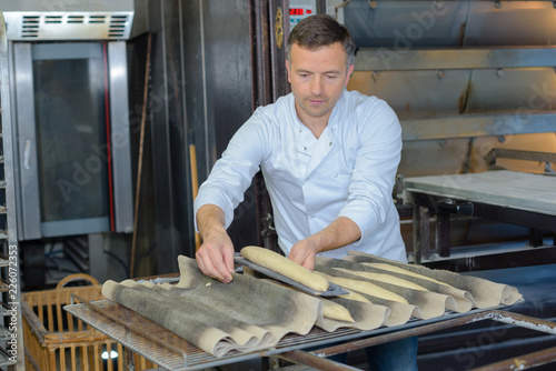 Leinwandbild Motiv Baker putting baguettes on tray to cook