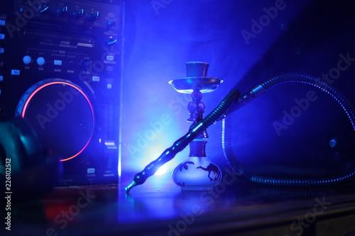 Shisha party club concept. Dj mixer with on dark nightclub background with stylish oriental shisha.