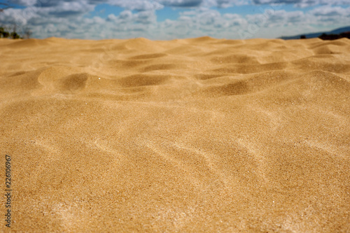 Golden sand in the hot and sunny desert. Yellow sand against the blue sky with clouds. © Viktoria