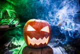 Scary Halloween pumpkin with blue and green smoke