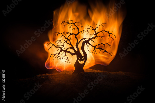 Leinwanddruck Bild Silhouette of scary Halloween tree with horror face on dark foggy toned fire. Scary horror tree Halloween concept.