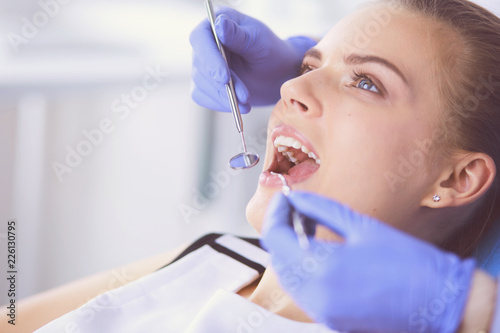 Leinwanddruck Bild Young Female patient with open mouth examining dental inspection at dentist office.
