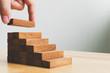 Leinwandbild Motiv Hand arranging wood block stacking as step stair. Ladder career path concept for business growth success process
