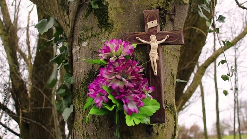 Close up of a catholic cross and a bouquet of pink flowers attached to a tree in the countryside. There is blowing through the flower and ivy leaves.