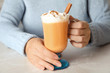 Leinwandbild Motiv Woman holding glass cup with pumpkin spice latte and whipped cream on light table
