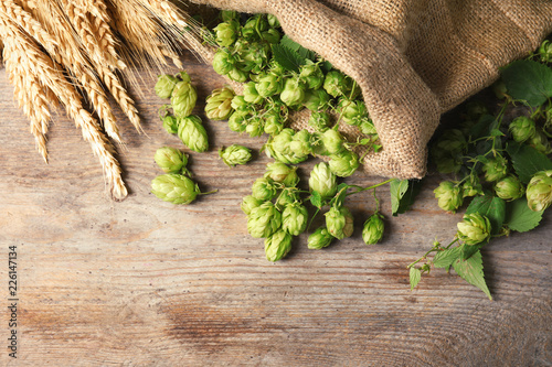 Leinwanddruck Bild Fresh green hops and wheat spikes on wooden background, top view with space for text. Beer production