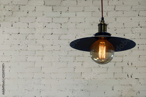 Industrial Style Light Pendant with Decorative Edison Filament Bulb on White Brick Wall Background © masummerbreak