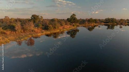 4K aerial shot, flight over amazing kwando river banks at golden hour, mirrored clouds in the water