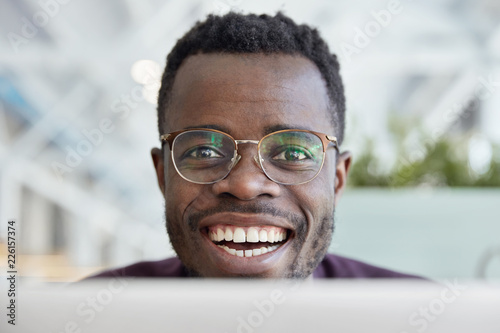Leinwandbild Motiv Close up shot of happy dark skinned man with broad smile, white teeth, wears transparent glasses for good vision, satisfied with work, being in good mood, poses indoor. People and positive emotions
