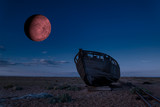 Digital composite image of Blood Red Moon over Abandoned fishing boat on shingle beach landscape - 226168752