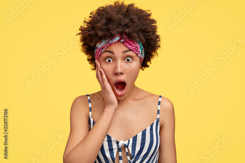 Leinwandbild Motiv Shocked housewife witnessed terrible crime or accident, holds palm near widely opened mouth, has Afro hairstyle, dressed in casual striped t shirt, isolated over yellow background. Omg concept