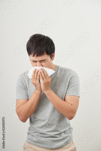 Foto Murales man is sick and sneezing with white background, asian