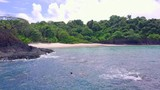 Two persons snorkeling at the coast with a sand beach and forest background. Boca, Chica, Panama. - 226186117