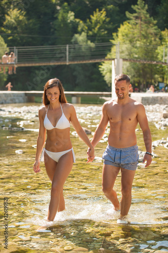 Foto Murales Active young couple chilling out in river  on a hot summer day standing and walking in water