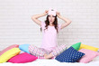 Beautiful girl with colorful pillows and sleeping mask sitting on white bed
