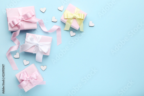 Foto Murales Colorful gift boxes with small hearts on blue background