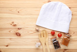 Chef hat with spices in jars and vegetables on brown wooden table