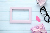 Pink wooden frame with gift box, glasses and perfume bottle. Boss day concept - 226192968