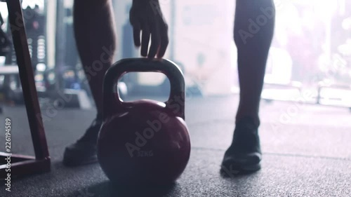 Sticker Fitness trainer placing kettlebells before Crossfit, weight training workout. dark atmosphere.
