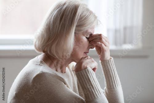 Leinwandbild Motiv Fatigued upset middle aged older woman massaging nose bridge feeling eye strain or headache trying to relieve pain, sad senior mature lady exhausted depressed weary dizzy tired thinking of problems