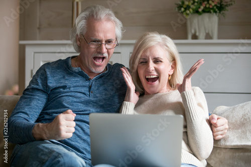 Leinwandbild Motiv Excited senior middle aged old couple watching celebrating amazing victory winning online auction bid or bet together, elderly mature man and woman motivated by good news looking at laptop screaming