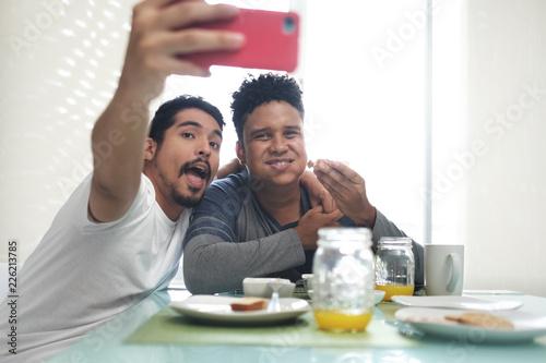 Leinwandbild Motiv Gay Couple Eating Breakfast Taking Selfie With Phone