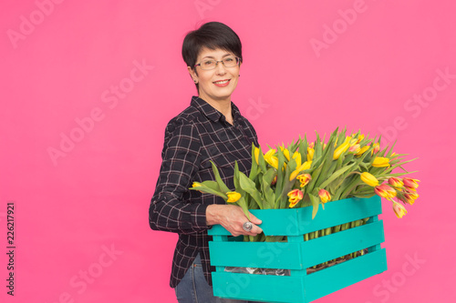 Middle-aged caucasian woman with box of tulips in pink studio. - 226217921