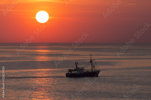 Fishing trawler on the North Sea at sunset