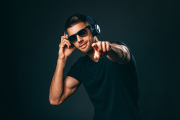Handsome man with headphones in studio on dark background