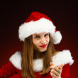 Beautiful woman in Santa Claus clothes pointing