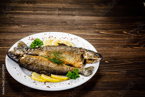 Fish dish - fried fish fillet on wooden table - 226241304