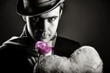 Mysterious men with toy and rose on grey background. Image on black and white color