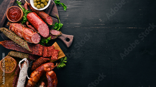 Assortment of salami and snacks. Sausage Fouet, sausages, salami, paperoni. On a black wooden background. Top view. Free space for your text. - 226245181