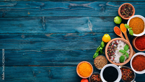 Spices and herbs on a blue wooden table. Basil, pepper, saffron, spices. Indian traditional cuisine. Top view. Free copy space.