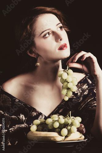 Leinwanddruck Bild Portrait of beautiful rich woman with grapes.