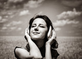 Young smiling girl with headphones at wheat field. Image in black and white color style - 226255179