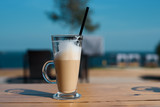 Glass mug with a latte with a tube on a wooden table, with a black straw - 226258929