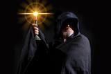 eine mystische Gestalt mit Kapuze hält ein Licht in die Höhe