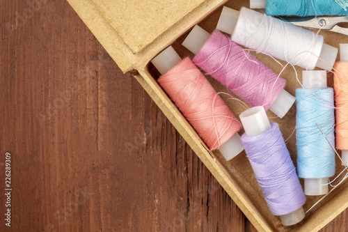 Overhead closeup photo of sewing box with threads and a needle, with copy space