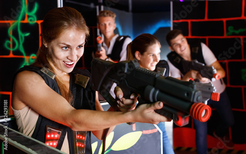Leinwanddruck Bild Portrait of exciting girl with laser pistol playing laser tag in dark room