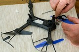 hands of man repairing small black drone with blue propeller