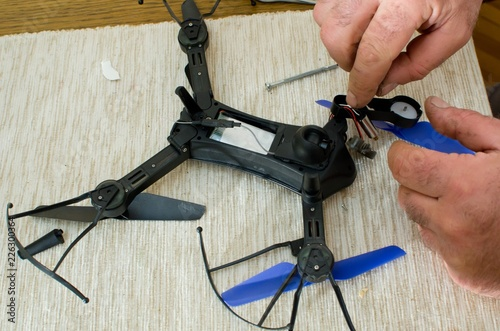 Fototapeta hands of man repairing small black drone with blue propeller