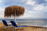 Holidays on the seaside. Two beach lounge chairs and straw parasol on the beach. Greece, Thassos island.